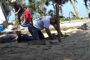 Bruce digs a hole with a coconut shell for a shelter foundation